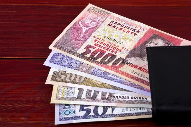 Old money from Madagascar in the black wallet. On a wooden background stock images