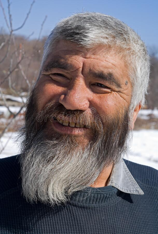 Old Mongoloid Man 17. A portrait close-up of the old smiling men with grey beard. Small indigenous people of Russian Far East stock images
