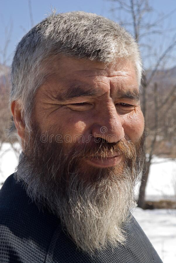 Old Mongoloid Man 3. A portrait close-up of the old smiling men with grey beard. Small indigenous peope of Russian Far East royalty free stock image
