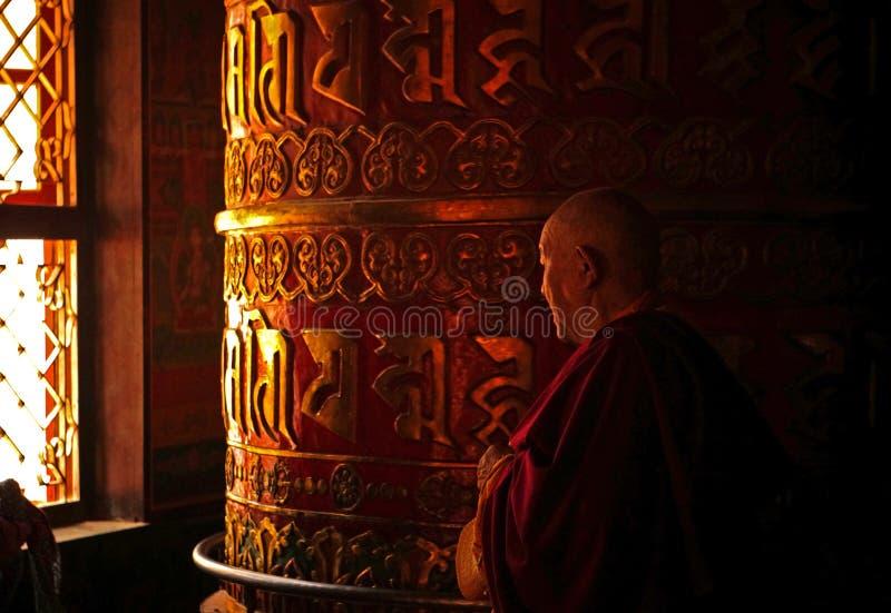 Old Monk Rotating a Prayer Wheel stock image