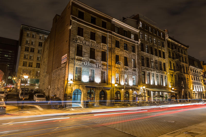 Old Montreal at Night. MONTREAL, CANADA - 17TH MAY 2015: A view of buildings along Rue de la Commune in Old Montreal at night. The trails of traffic can be seen stock photography
