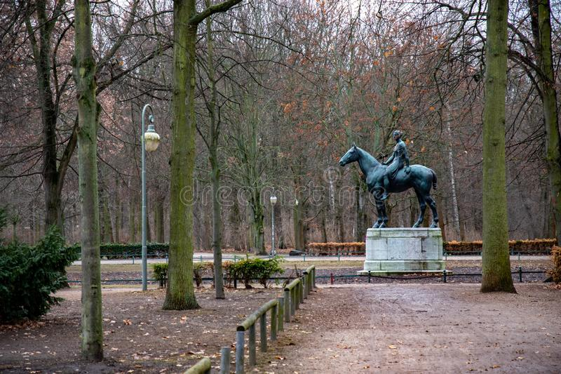 Old monument and rows of trees and retro streetlights in Tiergarten park of Berlin Germany. Tranquil landscape with nobody in autumn season. View to antique stock image