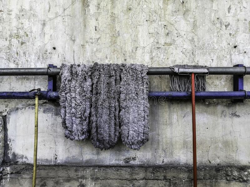 Old mop lay on the steel rail to dry, Old faucet and old rubber hose, Old cement wall background stock image