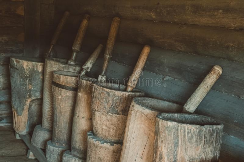 Old mortars with pistils in them. Old home utensils  for grains grinding. Old wooden mortars with pistils in them. Old home utensils  for grains grinding stock photography