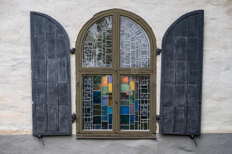 Old mosaic window with cover doors from an old church in Sweden royalty free stock image