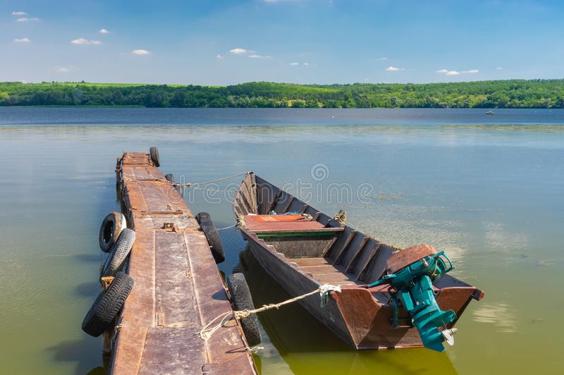 Old motor boat near rusty pier on a Dnipro river. In central Ukraine stock photography