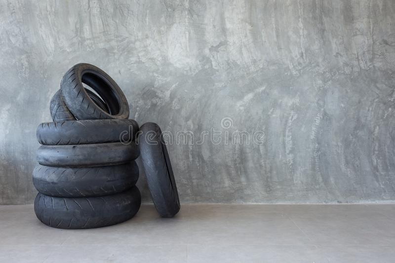 Old motorcycle tire on Bare cement wall. Detail stock images