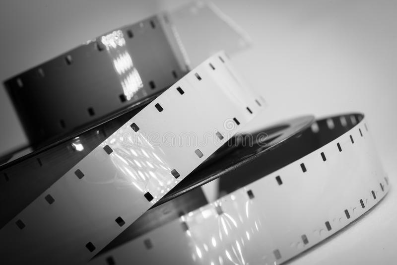 Old movie camera film reel strip. Black and white with studio lights reflection stock image