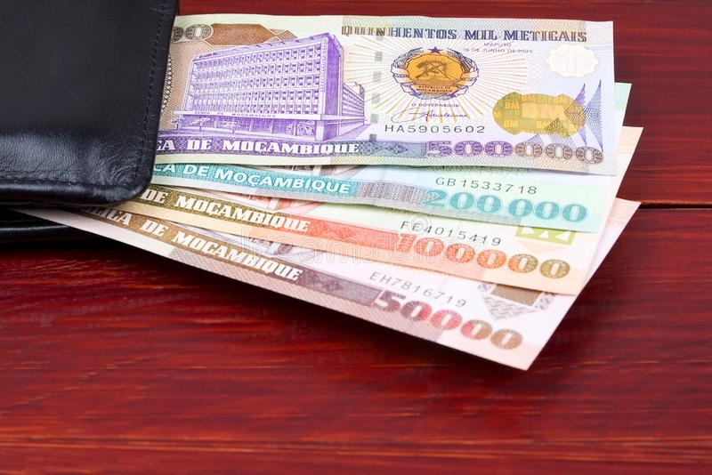 Old Mozambican money in the black wallet. On a wooden background stock photos