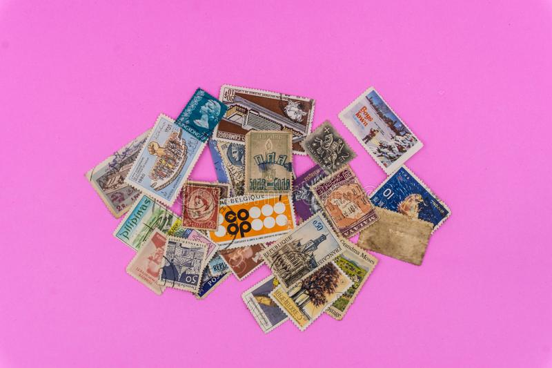 Old Multi Nation Stamps collection on pink Background stock photo