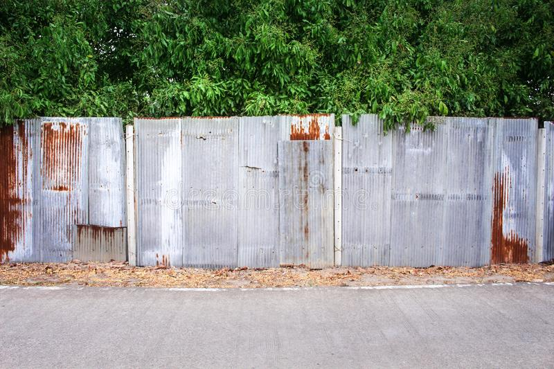 Old multicolored rusty zinc fence in vertical patterns texture with high longan green trees and concrete road background. Close up Old multicolored rusty zinc stock photography