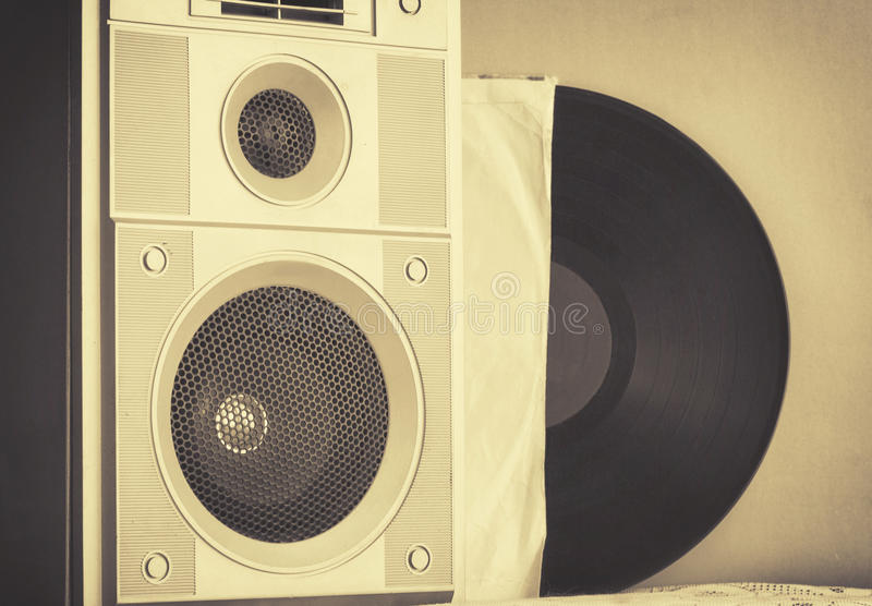 Old music speaker in foreground, record in paper cover royalty free stock image
