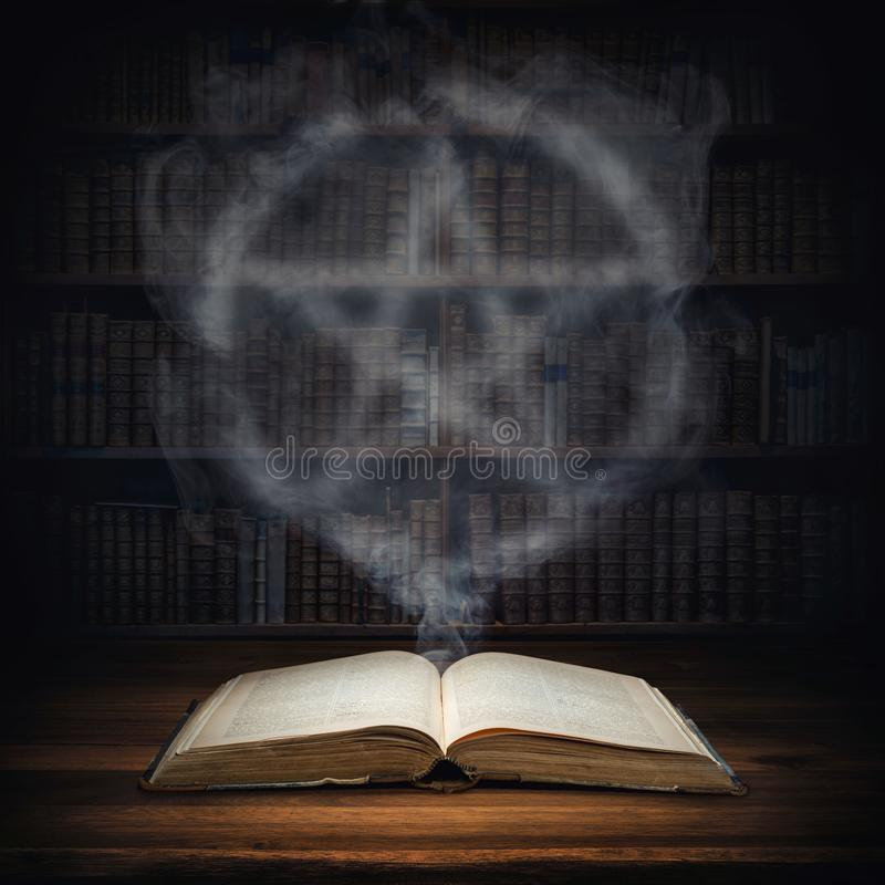The old mysterious book and the smoke coming out of it is a sign of the pentagram. Occult, esoteric, divination, magic concept stock photo