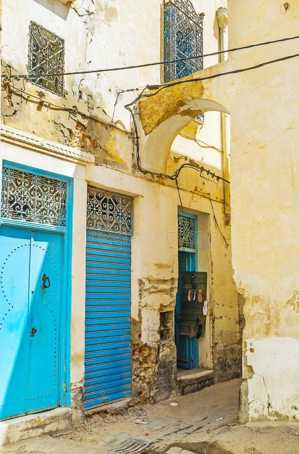 The backstreets of Sfax, Tunisia. The old narrow backstreet with bright blue doors of workshops and small shops, Sfax, Tunisia royalty free stock image