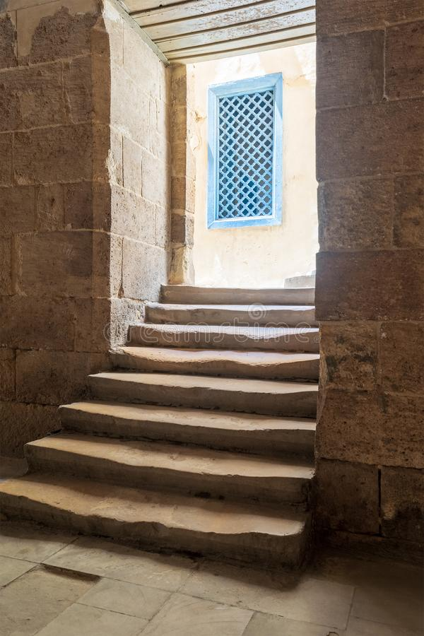 Old narrow dark passage and staircase leading to outdoor small lobby with blue wooden windows. Aged narrow dark vaulted passage and staircase leading to outdoor royalty free stock image