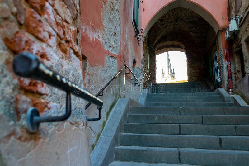 Old narrow street with shriveled brick walls, cement stairs and a black metal handrail pointing up towards an archway royalty free stock photo
