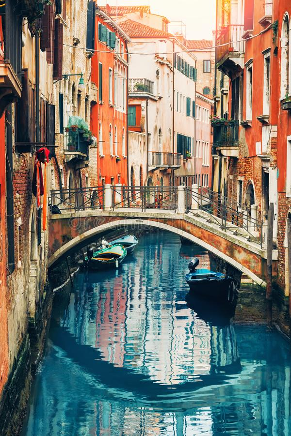Old narrow water canal with boats and bridge in Venice, Italy stock images
