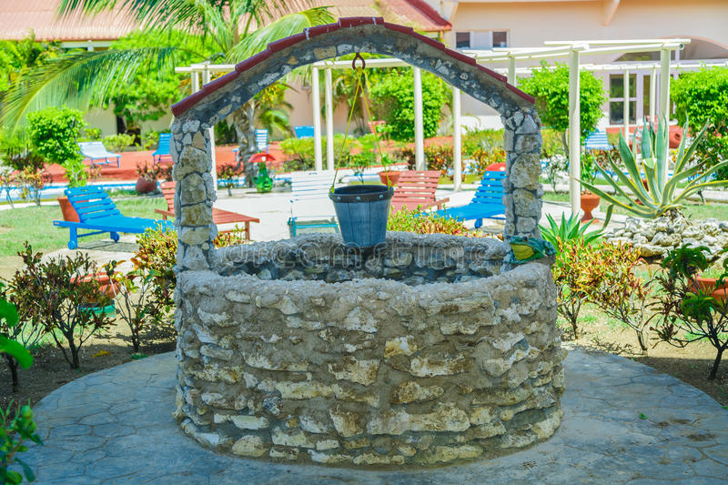 Old natural vintage stone will with pail standing in outdoor spa tropical garden grounds. Cayo Coco island, Cuba, Sep 2, 2015 view of old natural vintage stone royalty free stock photo