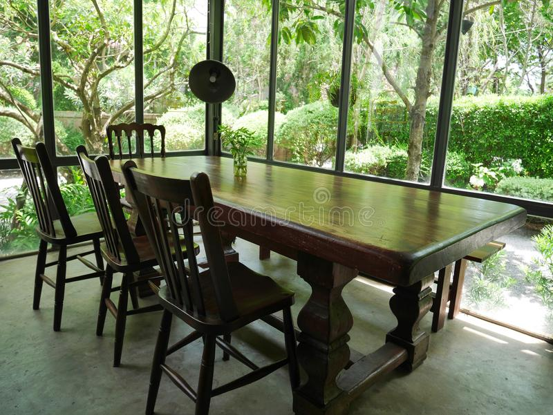 Old natural wooden table and chairs in vintage style inside a glass house stock photos