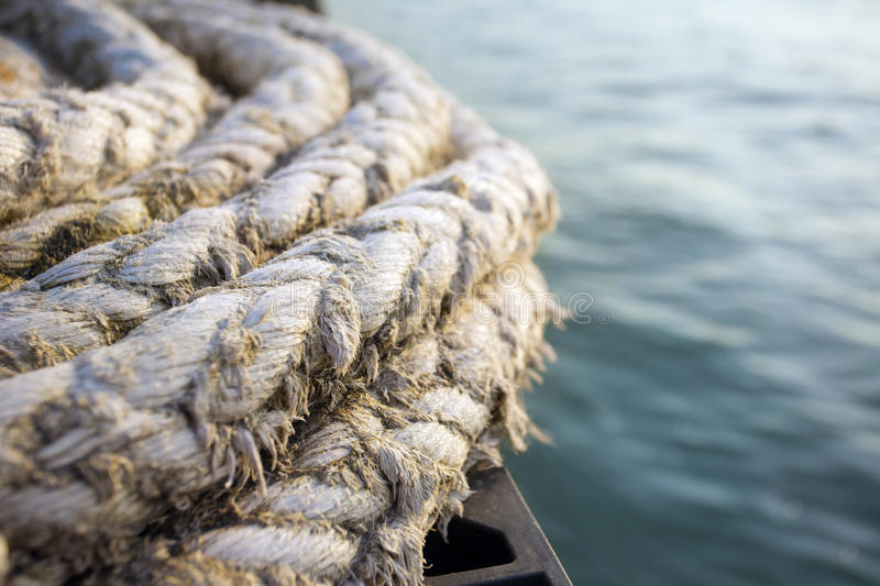 Old naval rope on a pier. Against blue water stock photos