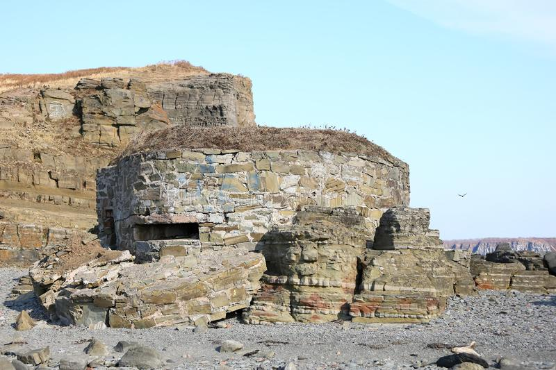 Old navy fortification made of coastal stones in the rocks.The coast of the Sea of Japan, Russia, Vladivostok, Tobizina Cape. Old navy fortification made of royalty free stock photos