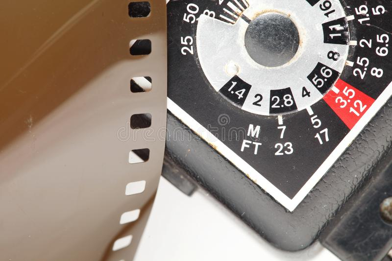 Old negative filmstrip. The old and dirty negative filmstrip and speed light dial panel represent the photography and camera support equipment concept related royalty free stock images