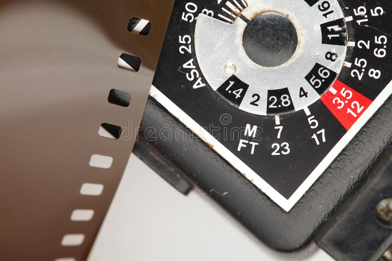 Old negative filmstrip. The old and dirty negative filmstrip and speed light dial panel represent the photography and camera support equipment concept related stock photo