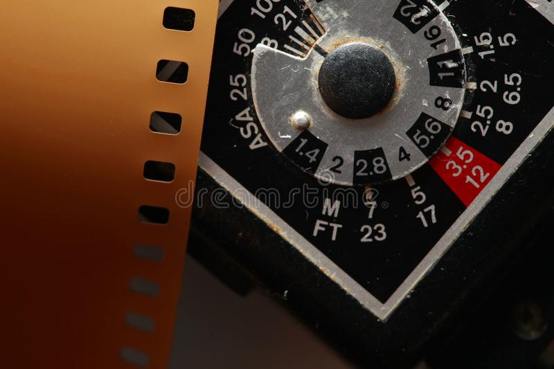 Old negative filmstrip. The old and dirty negative filmstrip and speed light dial panel represent the photography and camera support equipment concept related royalty free stock photos