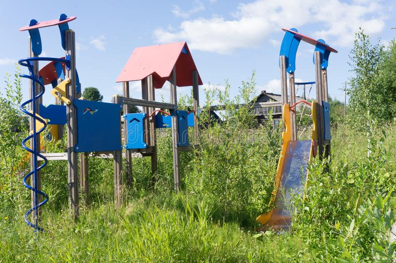 Old neglected playground equipment, overgrown with weeds. Old neglected playground equipment, overgrown with weeds royalty free stock images