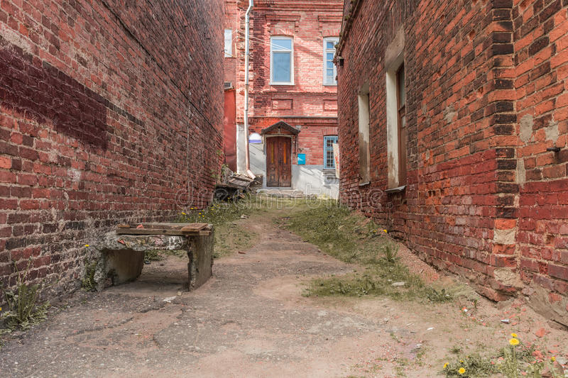 Old neglected quarter, walls of red brick destroyed form a perspective to the front door of a residential building stock photo