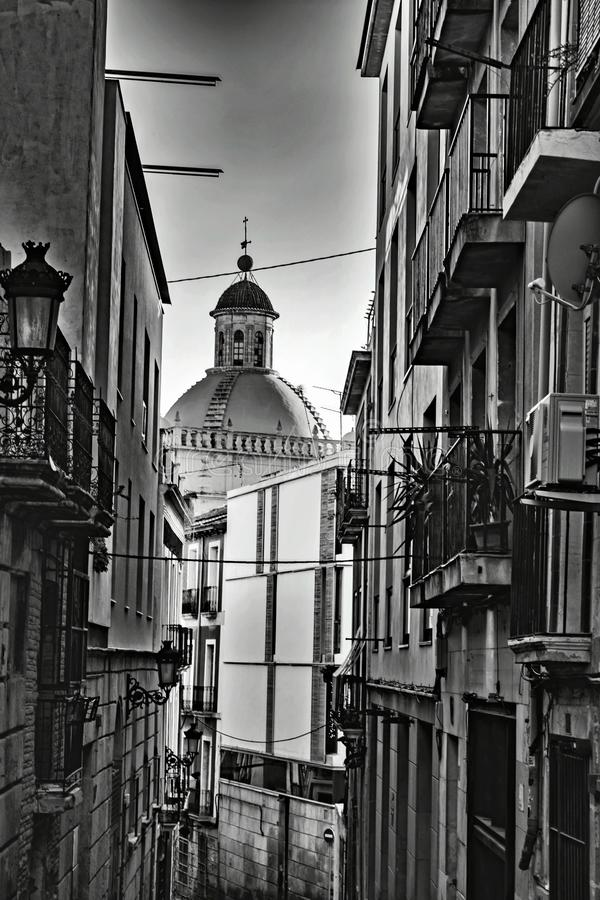 In an old neighborhood of Alicante. A dome closes the imaginary passage to a narrow street, adorned with balconies, lampposts and flower potsI royalty free stock photos