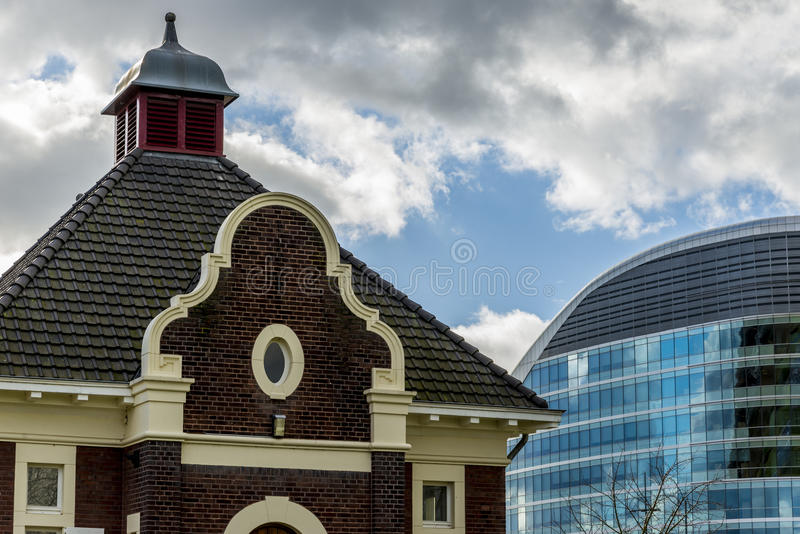 Old and new. Old waterpumphouse with modern office building in the background royalty free stock photography