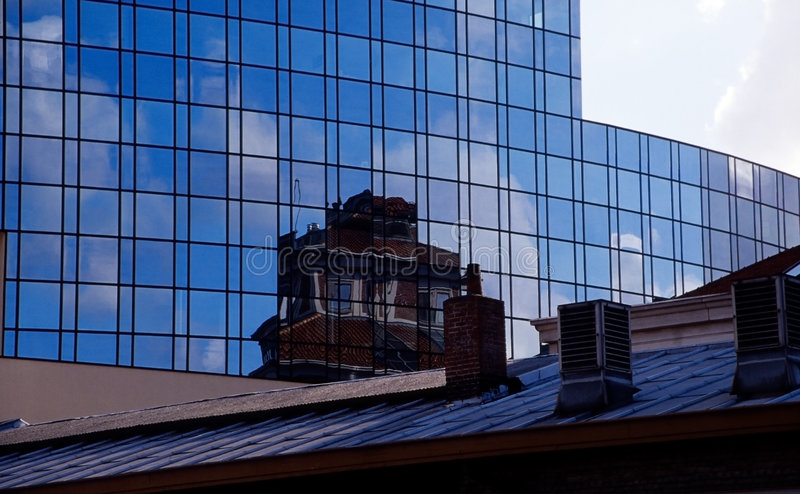 Old and new - buildings and reflections. Blue sky and small clouds stock photos