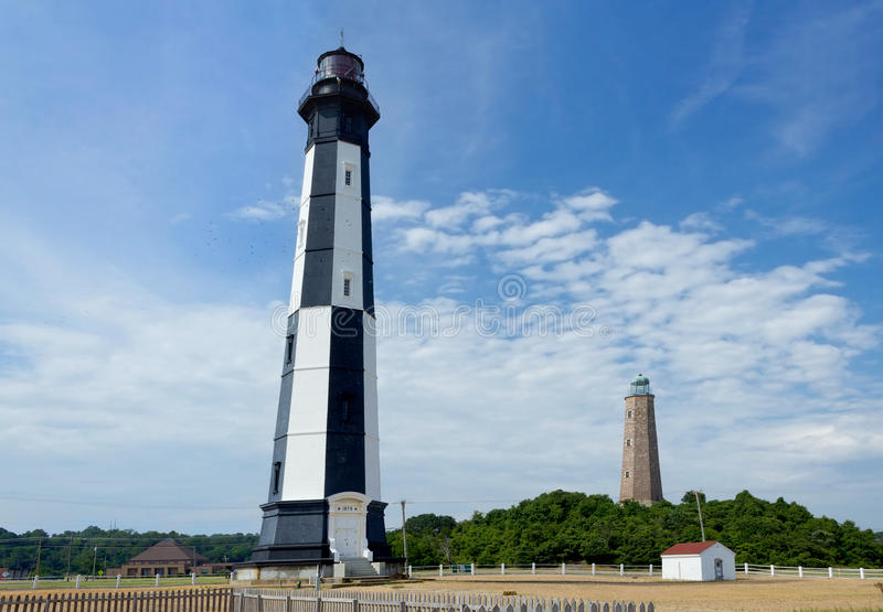 Old and New Cape Henry Lighthouses in Virginia Beach. A photo of Old and New Cape Henry Lighthouses in Virginia Beach with birds flying around New Cape Henry stock photo