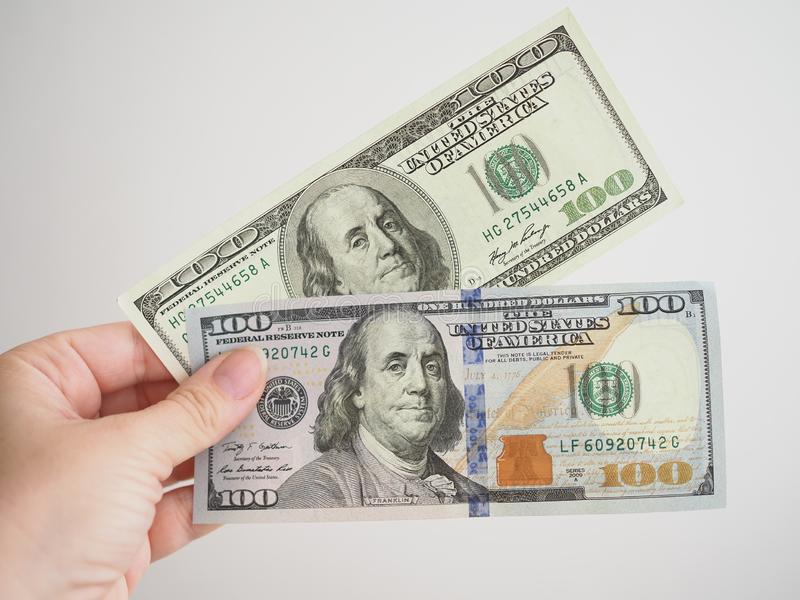 Old and new 100 dollar banknote in a woman`s hand royalty free stock image