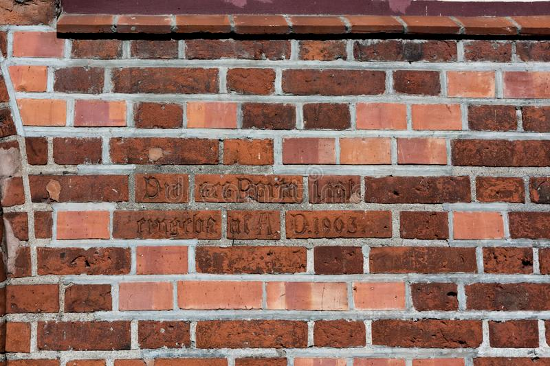 Old and new, red and white, inscription on old bricks. The brickwork of the old wall with splashes of new bricks. German inscription on old bricks stock images