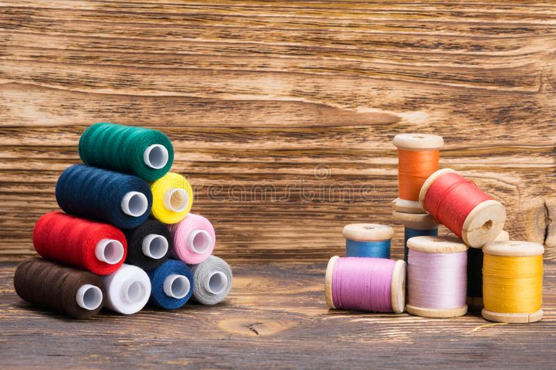 Old and new thread coils on a wooden royalty free stock image