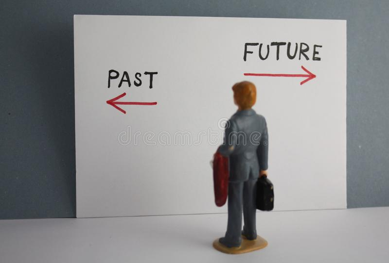 Old or new way decision concept. Miniature businessman back view past or future time vision plan stock images