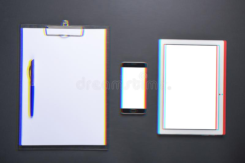 Old and new, White sheet of blank paper, smartphone, tablet, top view, glitch and anaglyph effect. Old and new, White sheet of blank paper, smartphone, tablet royalty free stock images