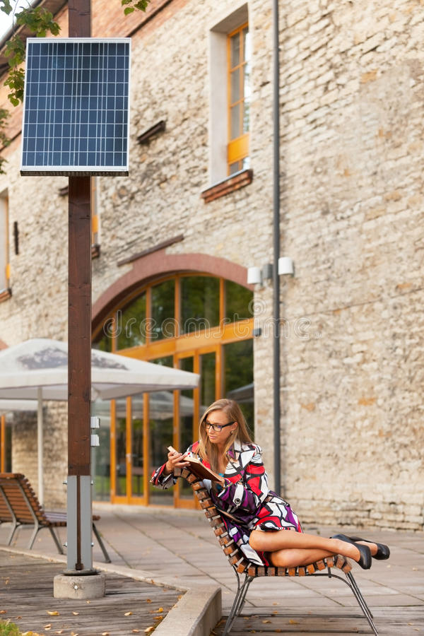 Old and new. Woman is reading book sitting under solar power plant royalty free stock image