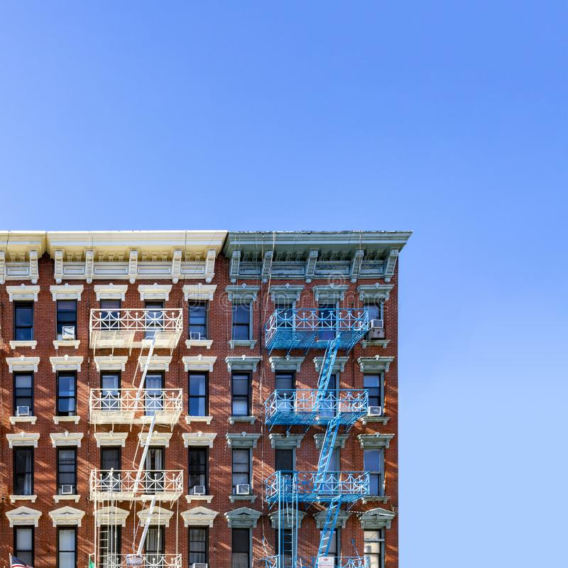 Free Old New York City Apartment Building Exterior With Fire Escapes And Windows And Empty Blue Sky Above Stock Images - 149317114