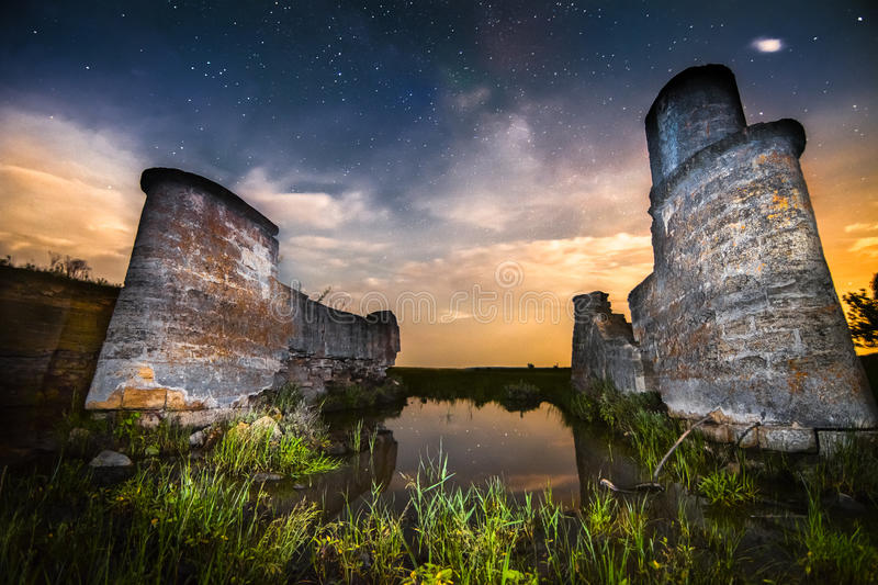 Old night castle wall ruins on lake reflections with stars sky a stock photography