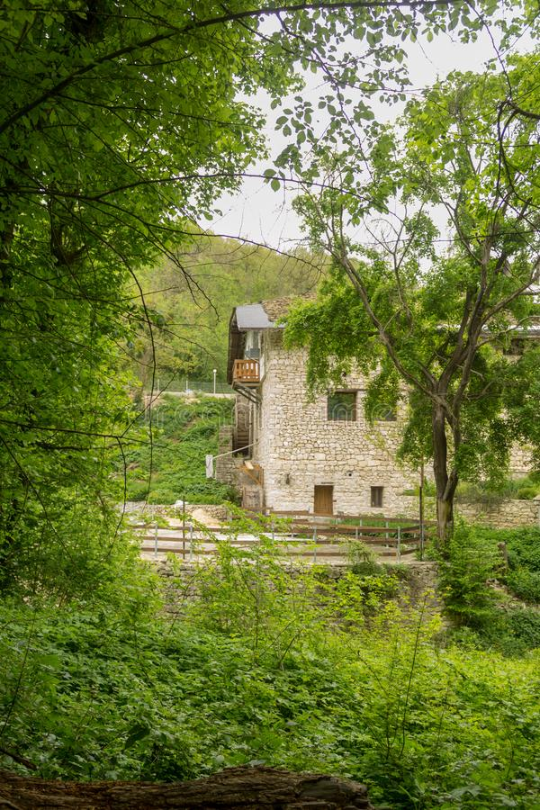 Old non working water mill in the forest in sunny day.  stock image