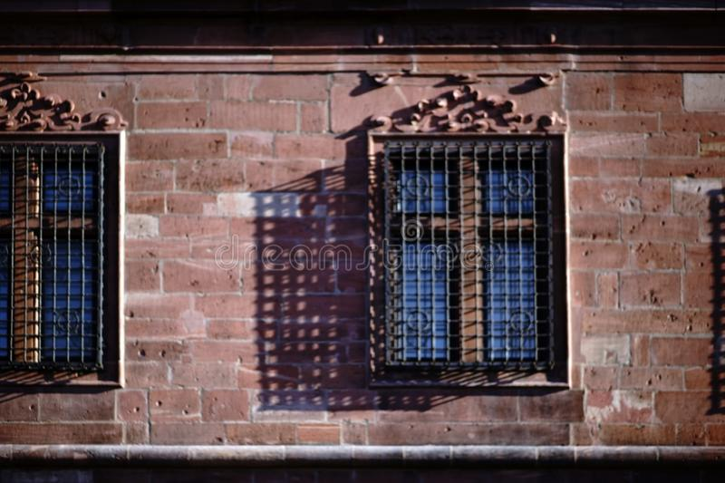 Iron grid casts shadows. An old and nostalgic iron grille in front of the window of a castle casts an abstract shadow stock photos