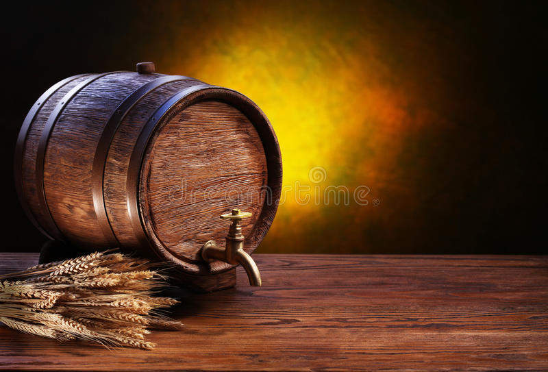 Old oak barrel on a wooden table. Behind blurred dark background royalty free stock photos