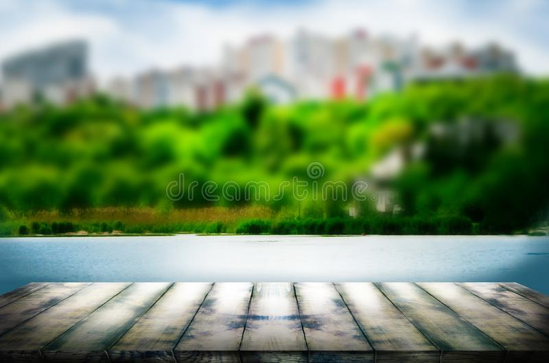 Old oak pier in perspective against the background of a blurred landscape with a lake. The template can be used to display your royalty free stock photos