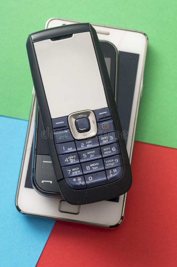 Old and obsolete cellphone on a RGB background. From above stock image