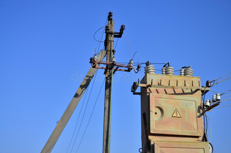 Old and obsolete electrical transformer against the background of a cloudless blue sky. Device for distribution of supply of high stock images