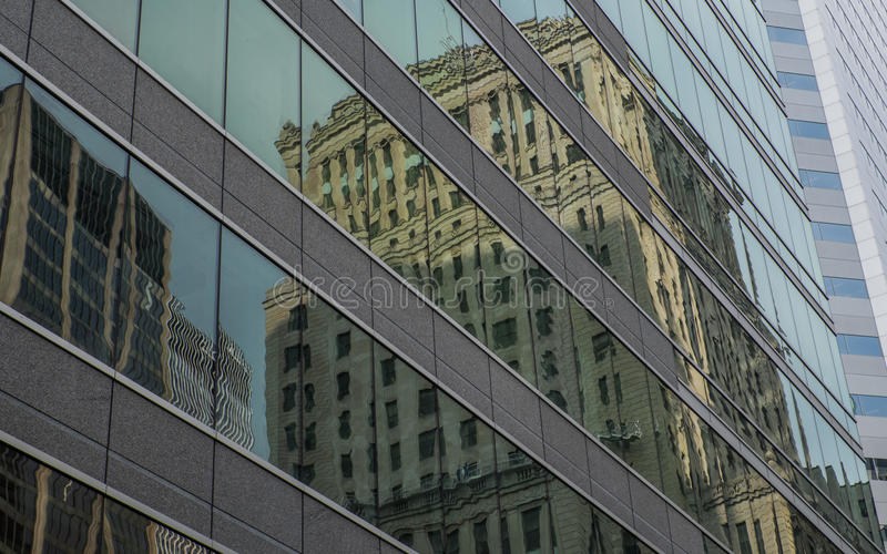 Old office buildings reflected in the glass of a modern office building stock image