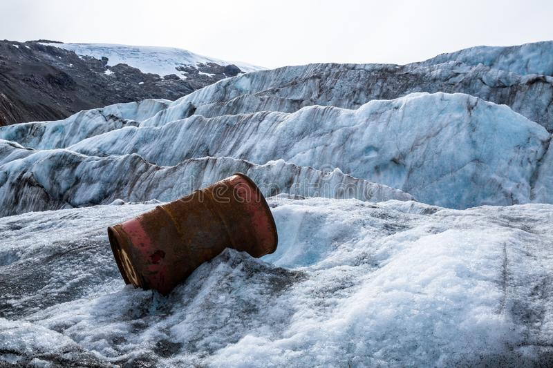 Trash on a glacier. Old oil barrel from mining camp in the mountains of British Columbia left to rust on the Berendon Glacier. An old oil drum discarded from a stock image